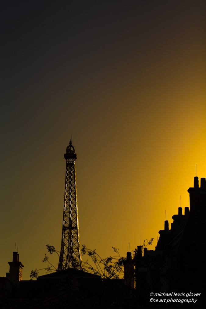 The warm glow of late afternoon light illuminates the Eiffel Tower at EPCOT.