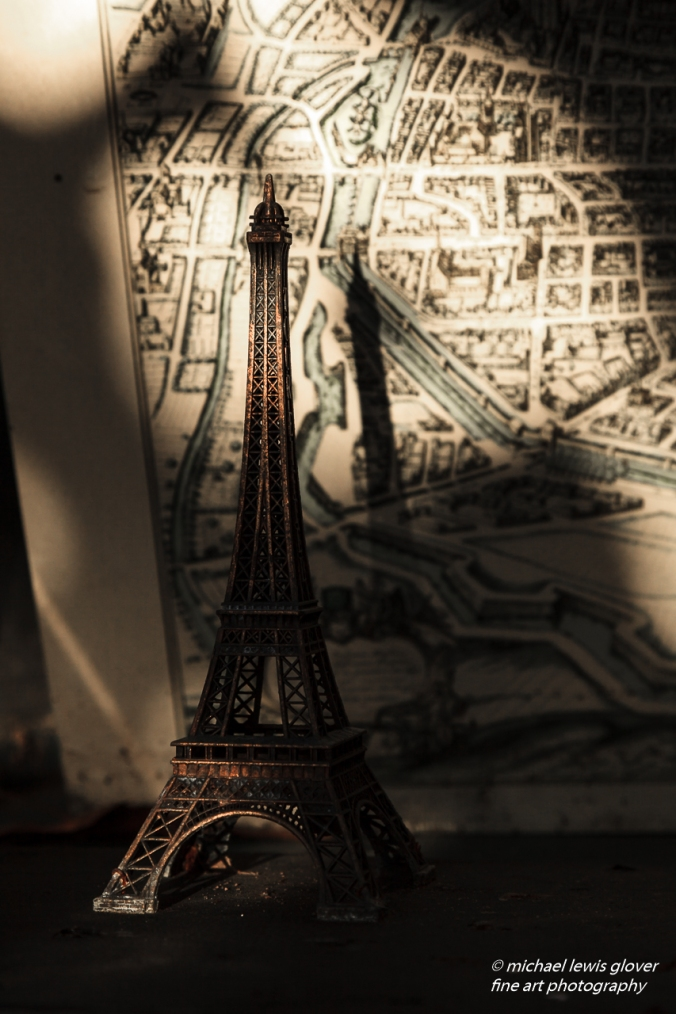 A miniature Eiffel Tower is illuminated by a late afternoon sun, casting shadows on its background.